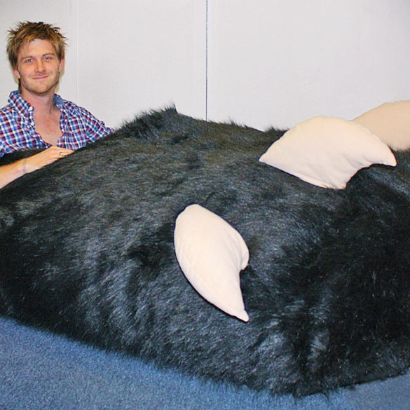 PIC FROM CATERS NEWS - (PICTURED: TOM BODDINGHAM SAT IN THE GIANT SLIPPER) - How about this for a massive SLIP-per up... A man who ordered a special slipper to fit his oversized foot was sent a size 1,450 - after manufacturers failed to spot a decimal point in his order. Tom Boddingham, 27, has a size 13 right foot while his left is slightly bigger and measures a size 14-and-a-half. But when he ordered his custom-fit slipper manufacturers in China misread size 14.5 and accidently made a whopping 7ft long size 1,450 - or XXXXXXXXXXXXXXXXL. SEE CATERS COPY